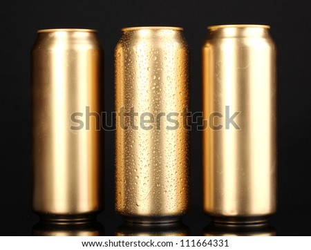 golden cans with water drops isolated on black