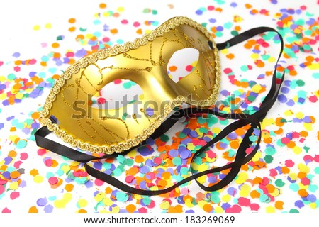 Golden carnival mask with ribbons on a confetti background - stock photo