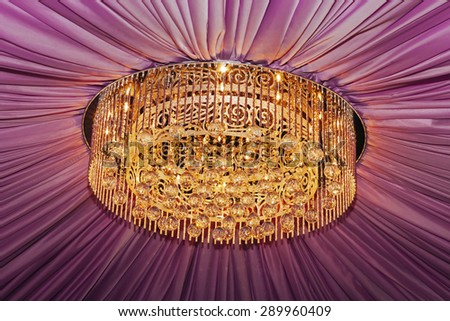 Golden chandelier with violet curtain, closeup view