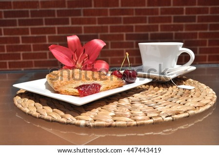 Golden cherry turnover and red cherries on a white plate, white tea cup with tea bag,red lily on natural weaved place mat. Brick wall in the background. - stock photo