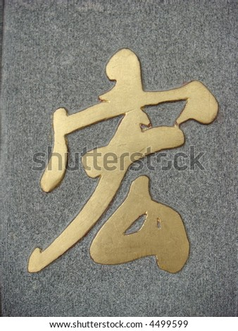 Golden Chinese Calligraphy on pebble surface: word for Great/Giant/Huge - stock photo