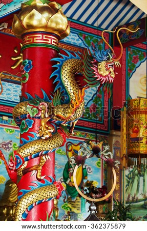 Golden Chinese Dragon Wrapped around red pole - stock photo
