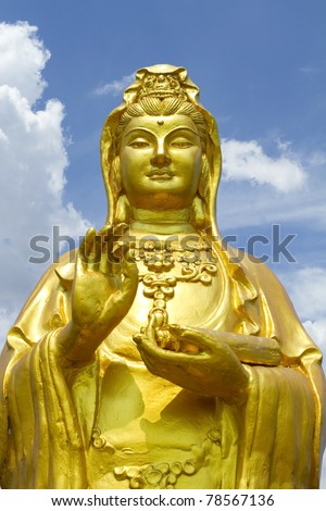 Golden Chinese goddess statue with blue sky - stock photo