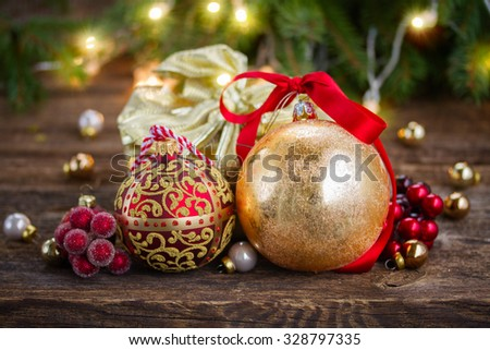 golden  christmas balls and gift box with defocused christmas lights in background - stock photo