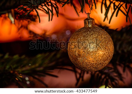 Golden Christmas bauble on a tree with glittering lights - stock photo