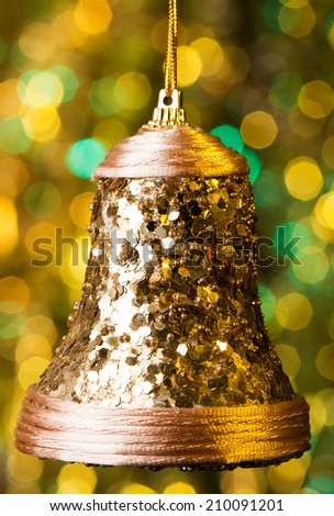 Golden Christmas bell decoration in front of defocused yellow and green Christmas lights.