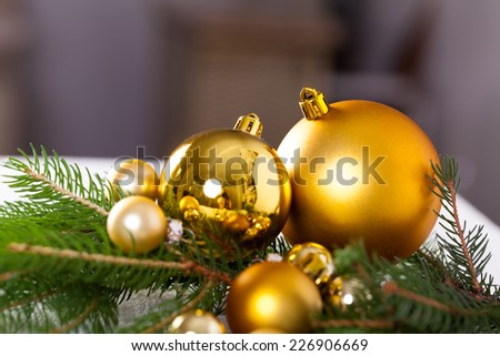 Golden Christmas decoration background with a variety of gold baubles and balls of different sizes and textures nestling on a branch of natural evergreen pine, shallow dof