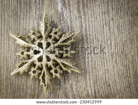 golden Christmas decoration with shining star on the wooden  background