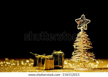 Golden christmas fir tree decoration and gifts on glitter background with black copy space - stock photo