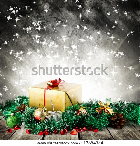 Golden christmas gift box with christmas balls on wood planks over dark background with light