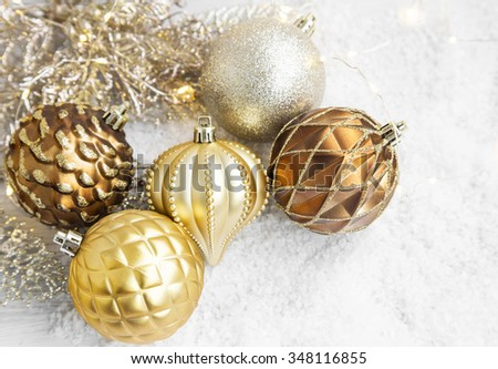 Golden Christmas ornaments with delicate globes and decoration in the snow