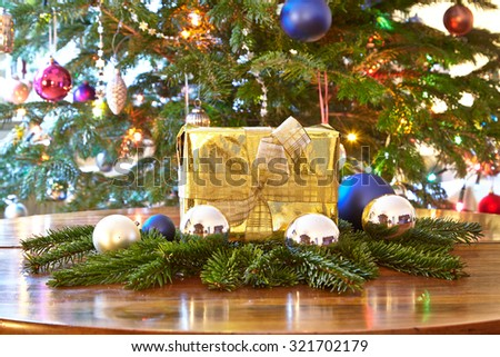 Golden christmas present and baubles, Christmas tree - stock photo