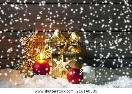 Golden christmas present, christmas ball, candle on pile of snow against wooden wall - stock photo