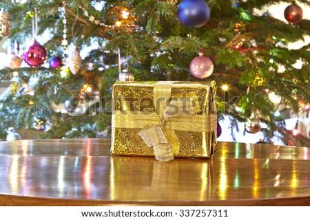 Golden christmas present, Christmas tree - stock photo