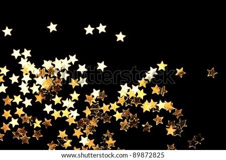 Golden Christmas stars on black background. - stock photo