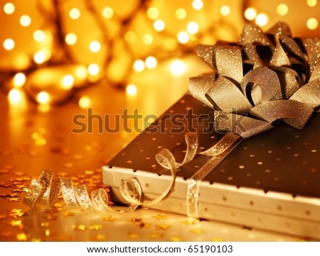 Golden Christmas tree ornament and holiday decoration with gift box & blur lights - stock photo