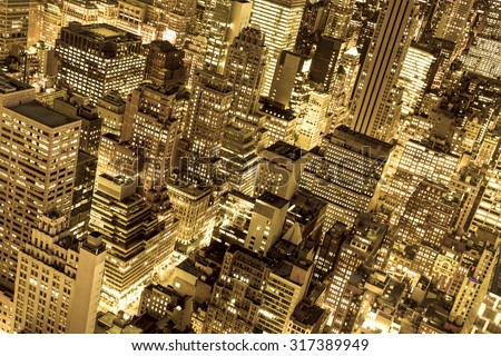 Golden cityscape of New York City buildings and lights at night - stock photo