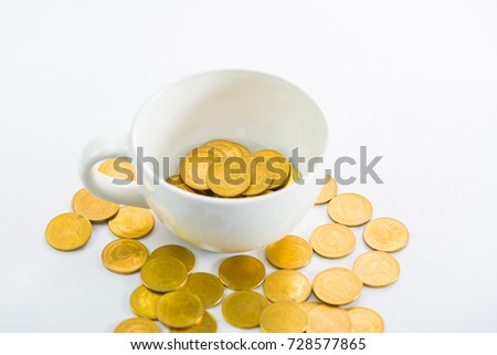 Golden coins in a white cup  of coffee on the white background, saving money concept.