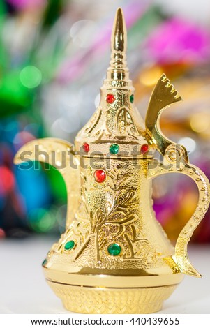 Golden colored Arabic Coffee pot in colorful  background.Ramadan Eid concept - stock photo
