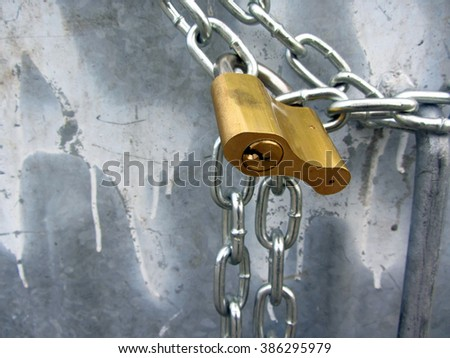 Golden colored padlock securing chains on grunge grey metal background. - stock photo