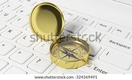 Golden compass on white laptop keyboard - stock photo