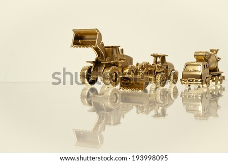 Golden Construction Vehicles with reflection with a yellow tinted filter. - stock photo