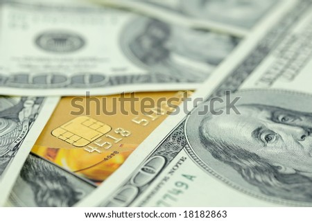 Golden credit card in US one hundred dollar bills - stock photo
