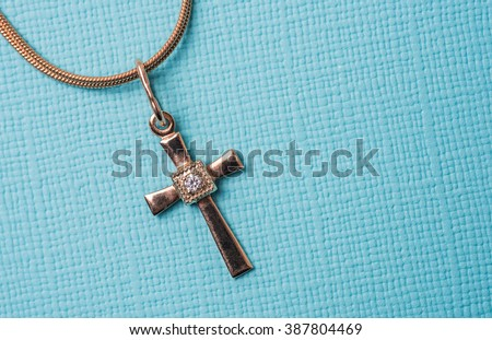 golden cross on a chain on a blue background - stock photo
