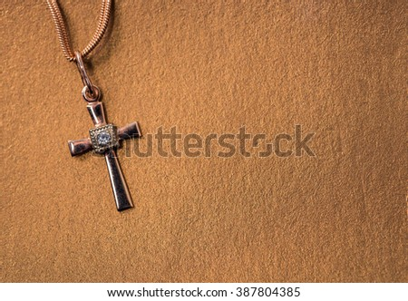 golden cross on a chain on a golden paper background - stock photo
