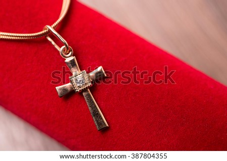 golden cross on a chain on a red background - stock photo