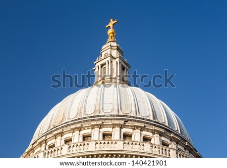 Golden cross on dome of St Pauls Cathedral in London England at dusk as the sun is setting low in sky. - stock photo