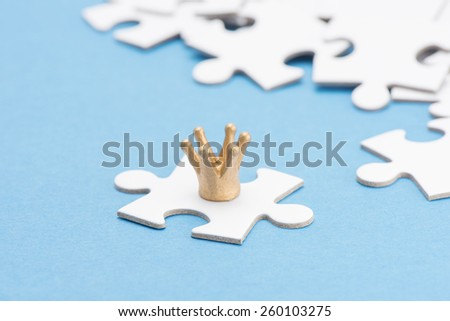 Golden crown on puzzle piece. Conceptual image of connection, solution and business strategy. - stock photo