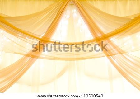 golden curtains on a window with illumination - stock photo