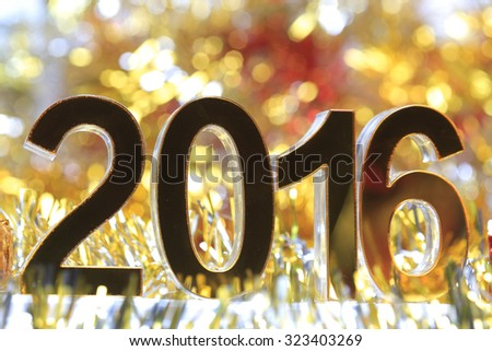 Golden 2016 3d icon in the christmas ornaments golden tinsel defocused blur backgrounds - stock photo