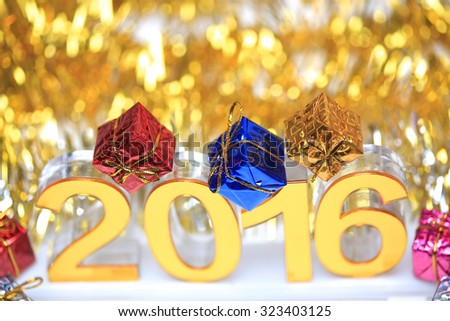 Golden 2016 3d icon with gift box in the christmas ornaments golden tinsel defocused blur backgrounds - stock photo