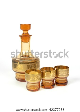 Golden decanter and three wine-glasses - stock photo
