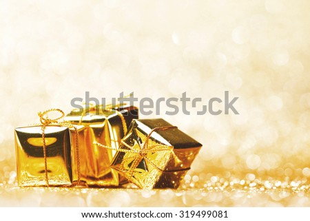 Golden decorative boxes with holiday gift on gold glitters background - stock photo