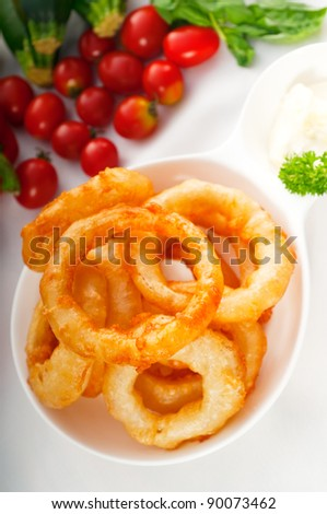 golden deep fried onion rings served with mayonnaise dip  and fresh vegetables oln background