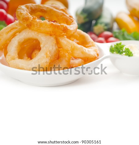 golden deep fried onion rings served with mayonnaise dip  and fresh vegetables oln background - stock photo