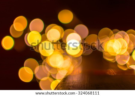 Golden defocused bokeh Christmas lights on a wooden support - stock photo