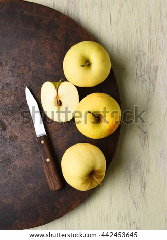 Golden Delicious apple still life with knife. Dark round surface on rustic table. - stock photo