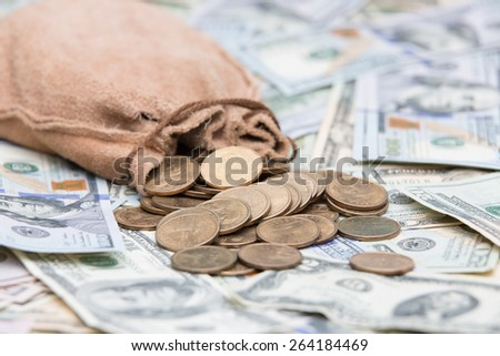 Golden dollar coins spilling from a hessian bag onto a background of US dollar bills with focus to the coins conceptual of wealth, winnings, growth returns, success, graft or money laundering concept - stock photo