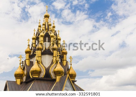 Golden dome of the Orthodox church  in Central Russia on the blue sky background partially covered with snow. - stock photo