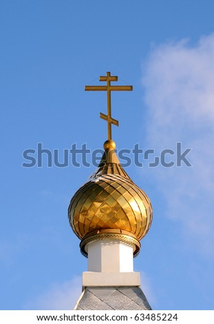 Golden dome of the Orthodox church  in Central Russia on the blue sky background partially covered with snow.