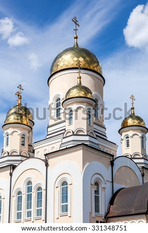 Golden domes of Russian orthodox church with cross against blue sky - stock photo