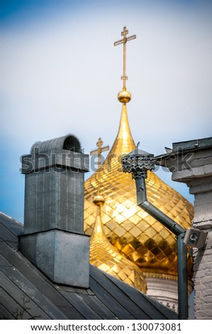 Golden domes with crosses of Russian Christian church shining behind old wooden roof with chimney. Contrast of grand and simple. Old architecture of Russia. Religion and holy places. - stock photo