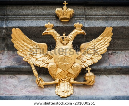 Golden double eagle on stone wall. Coat of arms of Russian federation - stock photo