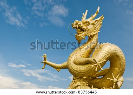 Golden dragon statue in blue sky background - stock photo