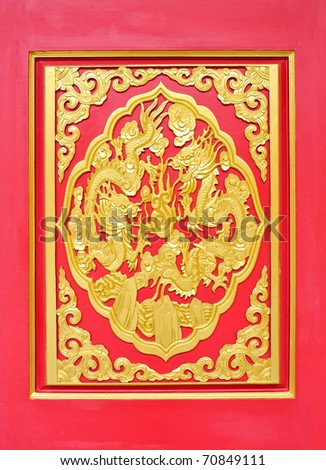 Golden dragon statue on the red wall of Chinese temple