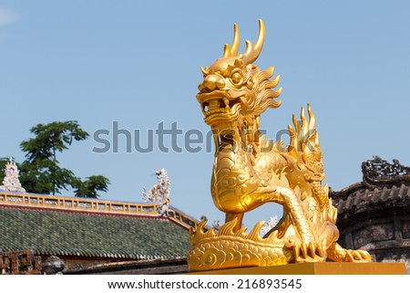 Golden dragon statue with blue sky background - stock photo